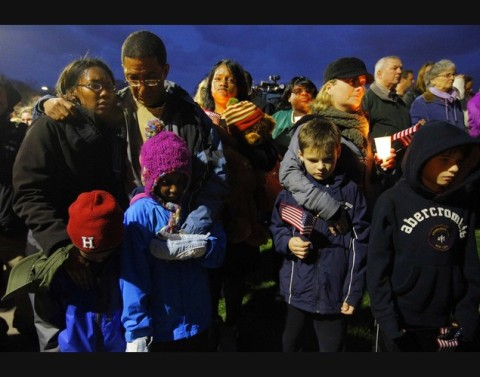 Local residents attend a candlelight vigil in the Dorchester neighborhood of Boston